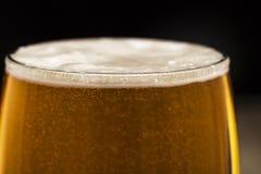 Vidro da cerveja com bolhas no close up preto Foto de Stock Royalty Free