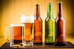 Vidro da cerveja com garrafas imagem de stock royalty free