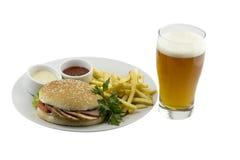 Vidro da cerveja, de um hamburguer, de batatas fritas e de molho foto de stock