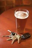 Vidro da cerveja e das chaves na tabela da barra Fotos de Stock Royalty Free