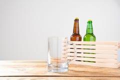 Vidro da cerveja e das duas garrafas em uma tabela de madeira Vista superior Foco seletivo Zombaria acima Copie o espaço molde bl foto de stock
