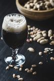Vidro da cerveja e dos amendoins no fundo de madeira Imagens de Stock