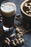 Vidro da cerveja e dos amendoins no fundo de madeira Fotografia de Stock