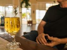 Vidro da cerveja - homem unfocused fotografia de stock