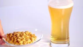 Vidro da cerveja no fundo branco com amendoins conservados vídeos de arquivo