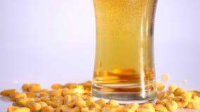 Vidro da cerveja no fundo branco com amendoins conservados Fim acima vídeos de arquivo