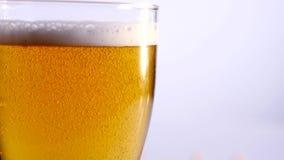 Vidro da cerveja que esvazia no fundo branco Fim acima video estoque