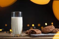 Vidro da foto do leite com cookies caseiros, fundo bonito com luzes no borrão imagem de stock