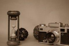 Vidro da hora com a câmera retro da foto fotografia de stock royalty free