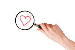 Vidro da lente de aumento na mão da mulher e no coração vermelho isolados no branco foto de stock royalty free