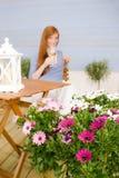Vidro da preensão da mulher do redhead do terraço do verão do vinho fotos de stock