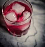 Vidro da secadora de roupa com os cubos vermelhos do cocktail e de gelo Imagem de Stock Royalty Free