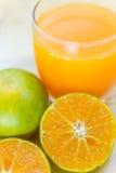 Vidro da tangerina fresca, suco de laranja com meio o alaranjado cortado Fotos de Stock