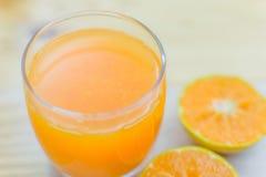 Vidro da tangerina fresca, suco de laranja com meio o alaranjado cortado Imagem de Stock