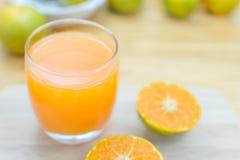 Vidro da tangerina fresca, suco de laranja com meio o alaranjado cortado Imagem de Stock Royalty Free