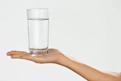 Vidro de água Conceito da saúde e da dieta A mão da mulher que guarda o vidro foto de stock royalty free