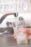 Vidro de água e torneira da cozinha Foto de Stock