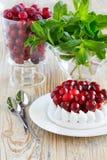 Vidro de arandos congelados Parcela de bolo da merengue com creme e arandos fotos de stock royalty free