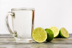 Vidro de cal e um vidro da bebida em uma tabela de madeira Fotos de Stock Royalty Free