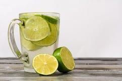 Vidro de cal e um vidro da bebida em uma tabela de madeira Imagem de Stock Royalty Free