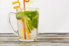 Vidro de cal e um vidro da bebida em uma tabela de madeira Imagem de Stock