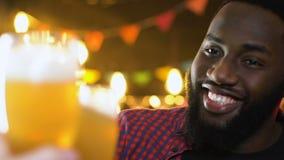 Vidro de cerveja afro-americano alegre do tinido do homem, celebração do partido de noite video estoque