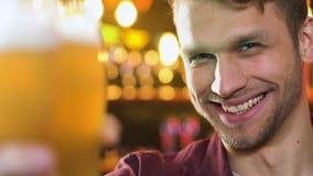 Vidro de cerveja masculino caucasiano feliz do tinido na barra, tempo de lazer com amigos filme