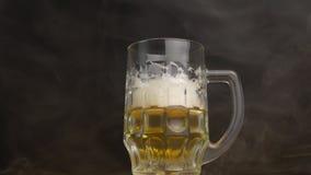 Vidro de cerveja torcido no que cerveja fresca é derramada, fumo, frescor, close-up, fundo preto, movimento lento, frescura vídeos de arquivo