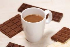 Vidro de chocolates do leite de chocolate e das barras na tabela fotografia de stock royalty free