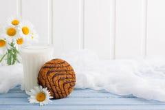 Vidro de cookies da aveia do leite com o ramalhete do chocolate das camomilas Imagem de Stock