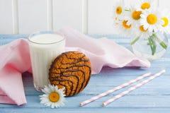 Vidro de cookies da aveia do leite com o ramalhete do chocolate das camomilas Fotografia de Stock