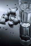 Vidro de cubos da água e de gelo em um fundo escuro Fotos de Stock Royalty Free