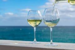 Vidro de derramamento do garçom do vinho branco no terraço exterior com mar v imagens de stock