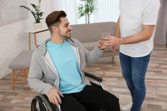 Vidro de doação voluntário da água a equipar em casa na cadeira de rodas imagem de stock royalty free