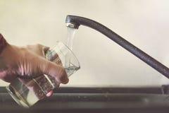 Vidro de enchimento com água da torneira Torneira e dissipador modernos na cozinha home Homem que derrama a bebida fresca ao copo fotografia de stock royalty free