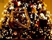 Vidro de encontro a uma árvore do ano novo foto de stock royalty free