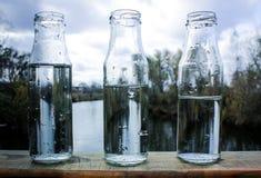 Vidro de garrafa de água no balcão Fotos de Stock