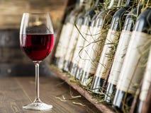 Vidro de garrafas do vinho tinto e de vinho em um fundo Imagens de Stock