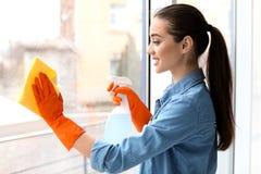 Vidro de janela da limpeza da jovem mulher fotos de stock royalty free