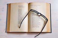 Vidro de leitura em um livro Fotografia de Stock Royalty Free