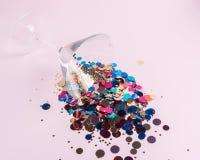Vidro de Martini com brilhos coloridos no fundo cor-de-rosa Conceito mínimo criativo do partido imagem de stock royalty free