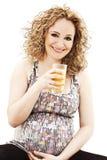 Vidro de sorriso da terra arrendada da mulher gravida do suco em h Foto de Stock Royalty Free