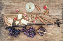 Vidro de varas de vinho branco, de placa do queijo, de uvas, de figos, de morangos, de mel e de pão no fundo de madeira rústico Foto de Stock