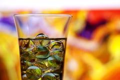 Vidro de vinho com mármores Fundo abstrato amarelo imagens de stock royalty free