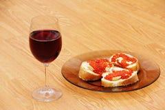 Vidro de vinho com vinho tinto e sanduíches com caviar vermelho Imagem de Stock