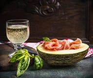 Vidro de vinho do Perl com presunto e melão, prato italiano tradicional na mesa de cozinha rústica Foto de Stock