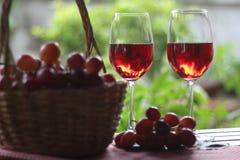 Vidro de vinho e uva vermelha em uma cesta foto de stock