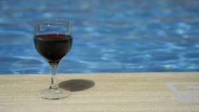 Vidro de vinho enchido com o vinho filme