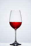 Vidro de vinho puro do vinho meio cheio com vinho tinto contra o fundo claro com reflexão Imagem de Stock Royalty Free