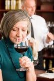Vidro de vinho sênior do gosto da mulher da barra de vinho Fotografia de Stock